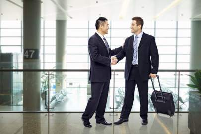Two men shaking hands, one with a briefcase